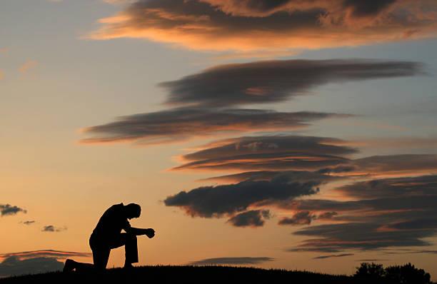 Evening Prayer Silhouette of Unrecognizable Man Kneeling stock photo