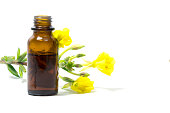 Yellow evening primrose (Oenothera biennis) flowers and a small bottle with oil, cosmetics and natural remedies for sensitive skin and eczema, isolated on a white background