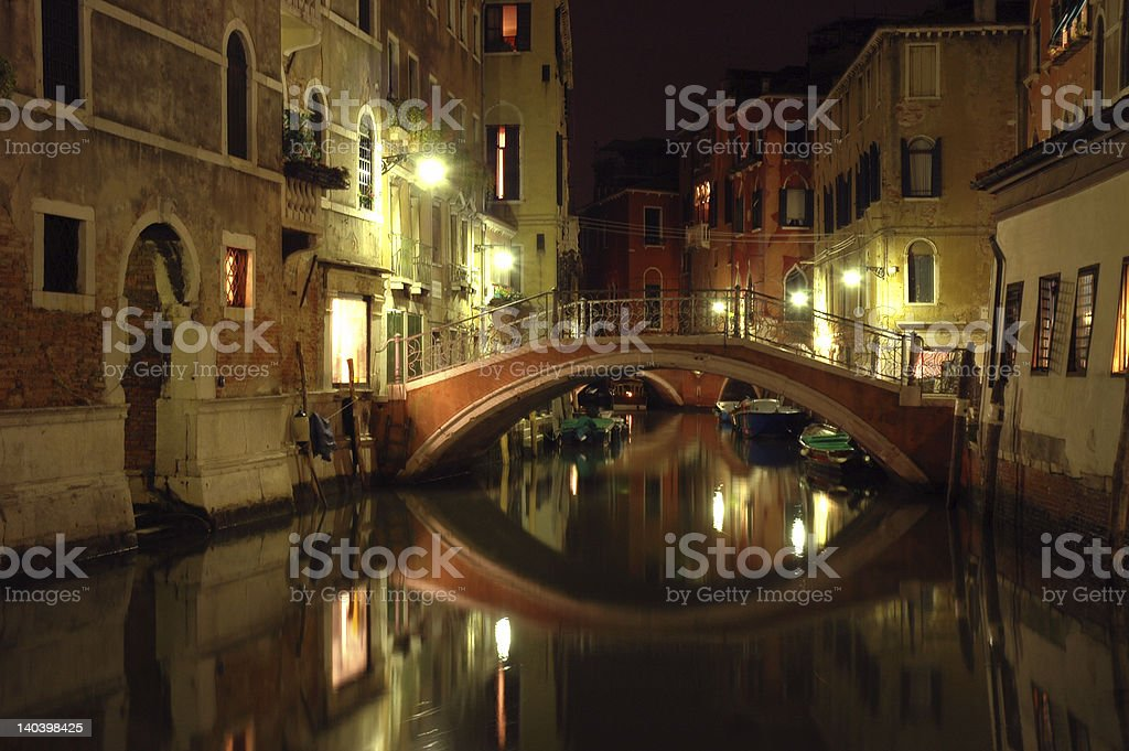Evening reflection of bridge in Venice canal stock photo