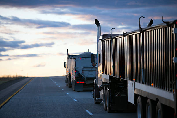 Evening road uphill with convoy semi trucks with bulk trailers stock photo