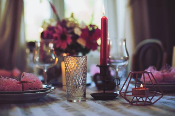am abend romantischen tisch für zwei personen mit kerzen und blumen in lila und weißen tönen. familienessen zu hause im sommer landhaus. - geheime garten parties stock-fotos und bilder