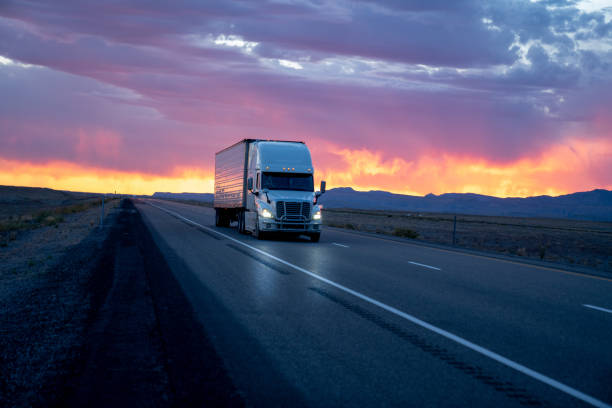 Evening Shot of a Semi-Trailer (white) traveling In Front of a Stunning Multi-Colored Cloudy Sunset or Sunrise on a Four Lane Desert Interstate Highway stock photo