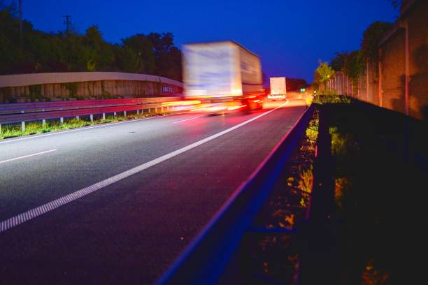 Evening shot of trucks doing transportation and logistics on a highway. Highway traffic - motion blurred truck on a highway motorway speedway at dusk stock photo