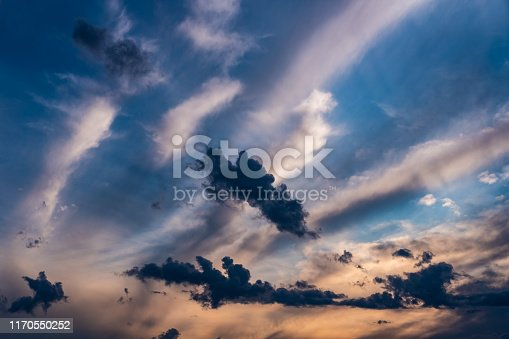 Evening sky at sunset background. Dark clouds hanging above horizon. Majestic cloudscape in blue, orange, violet shades. Grey cloudlets bringing rain. Countryside skyline in twilight time