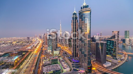 521078742 istock photo Evening skyline with modern skyscrapers and traffic on sheikh zayed road day to night timelapse in Dubai, UAE 1235257847