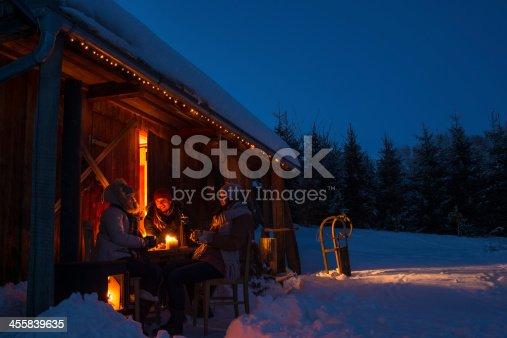 istock Evening snow winter cottage friends enjoy hot drinks 455839635