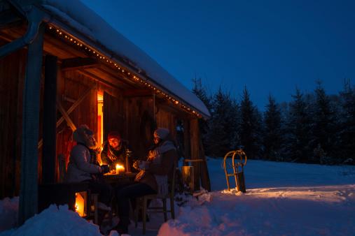 Evening snow winter cottage friends enjoy hot drinks