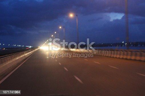 539234032 istock photo evening street lights,vehicles,highway, dusk, motion blurr and cloud sky 1071741964