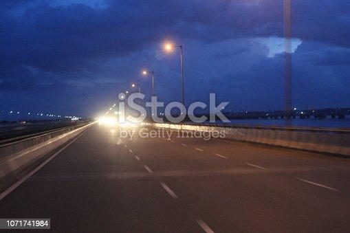 539234032 istock photo evening street lights,vehicles,highway, dusk, motion blurr and cloud sky 1071741984