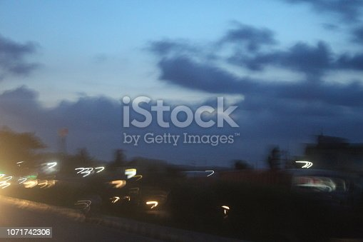 539234032 istock photo evening street lights,vehicles,highway, dusk, motion blurr and cloud sky 1071742306