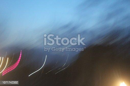 539234032 istock photo evening street lights,vehicles,highway, dusk, motion blurr and cloud sky 1071742332