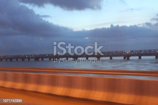539234032 istock photo evening street lights,vehicles,highway, dusk, motion blurr and cloud sky 1071742334
