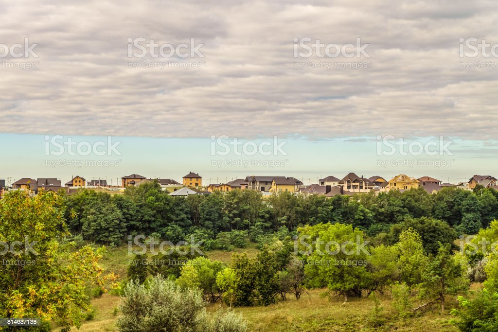 Evening suburban skyline. Buildings individual suburban housing in the eco-friendly green district. High layered clouds. stock photo