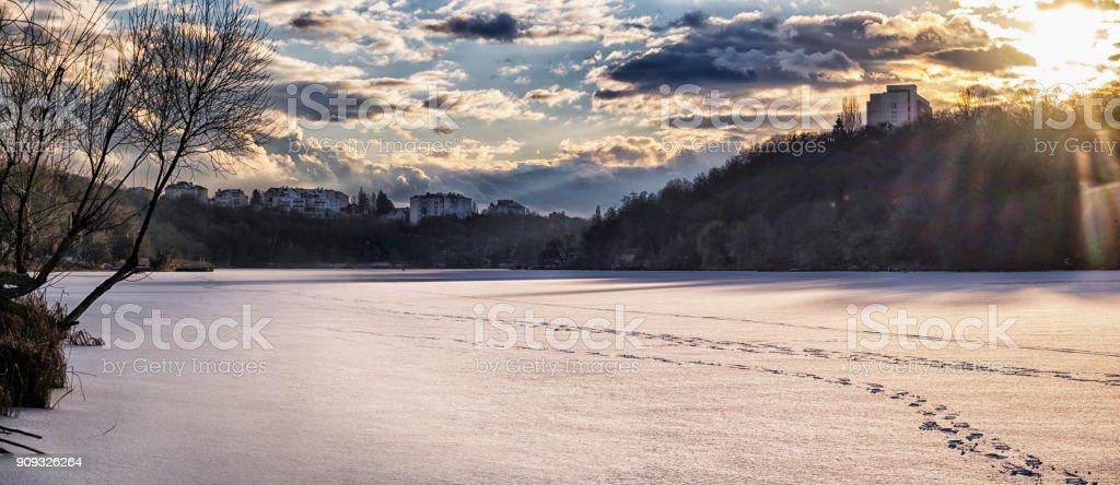 Evening sun illuminates the clouds over the frozen river (Ukraine, Vinnitsa, Southern Bug River) stock photo
