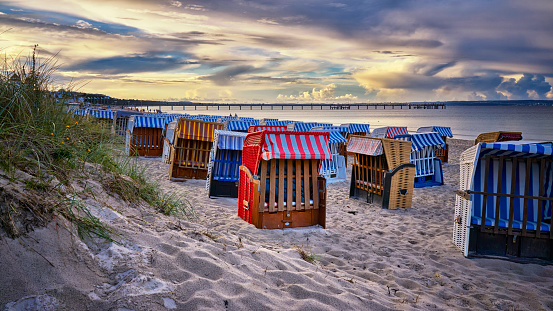 Evening sun with low light on beach filled with traditional wicker beach chairs.