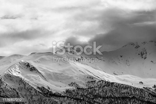 Evening sunlit snowy mountains and gray cloudy sky. Caucasus Mountains at winter. Georgia, region Svanetia. Black and white toned landscape.