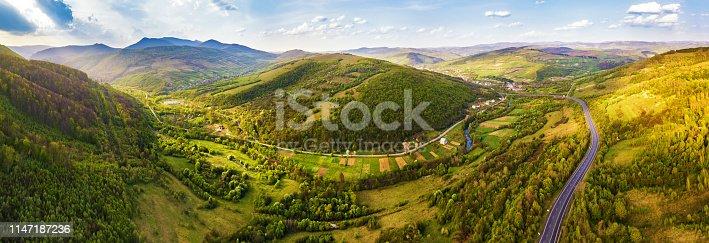1042711480 istock photo Evening sunlight on mountain hills. Roads in valley 1147187236
