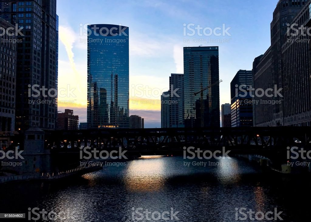 Evening sunset in winter reflects over Chicago River and Wells Street's elevated track. stock photo