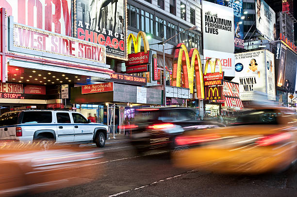 evening traffic on times square, new york city - mamma mia stock photos and pictures