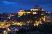 Esztergom, Hungary - October 7, 2015: Evening view of Esztergom Basilica on the top of the Castle Hill, and Parish Church of St. Ignatius of Loyola and Convent Church of the Exaltation of the Holy Cross at the foot of the hill. The Primatial Basilica of the Blessed Virgin Mary Assumed Into Heaven and St. Adalbert is the mother church of the Archdiocese of Esztergom-Budapest, and the seat of the Catholic Church in Hungary. The present church was laid in 1822 and consecrated in 1856. It is the biggest building in the country.
