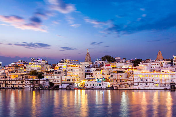 Evening view of  illuminated houses on lake Pichola in Udaipur Evening view of  illuminated houses on lake Pichola in twilight, Udaipur, Rajasthan, India lake pichola stock pictures, royalty-free photos & images