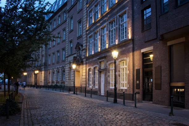 夕景の古い、歴史的建造物やデュッセルドルフ旧市街の通りの石畳。人々 は、ぼやけた動きで歩きます。 - ヨーロッパ文化 ストックフォトと画像