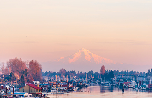 Evening view of the Columbia River with floating houses and boats and yachts moored at the berths on the background of the mountain Mount Hood
