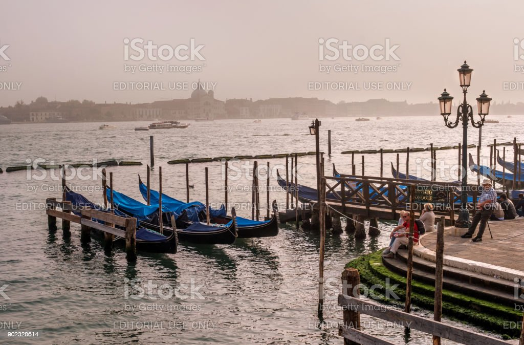 Evening view of the Grande Canal. Tourists admire the view. In the foreground are moored gondolas. stock photo