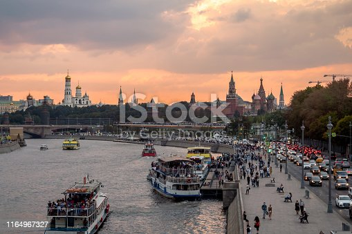 Evening view of the Moscow Kremlin, Zaryadye park and ships on Moscow river in front of rainy clouds