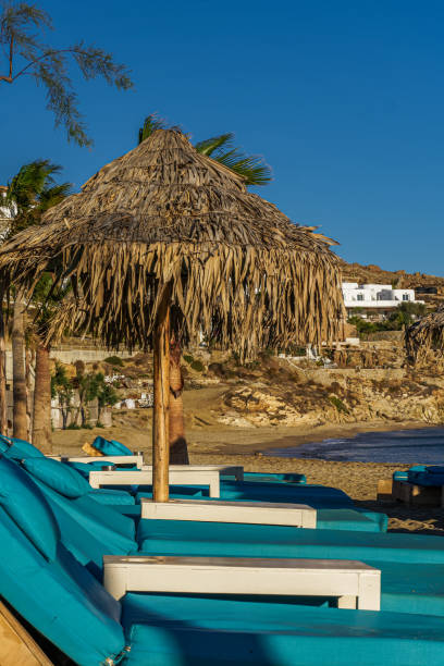 Evening view of wooden deck chairs with blue mattresses below bamboo sun protect umbrellas without crowd at Mykonos Greece Paradise Beach. stock photo