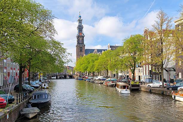 evening view on the western church in amsterdam - westerkerk stockfoto's en -beelden