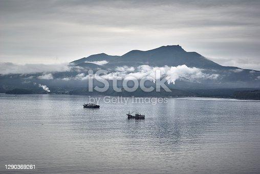 istock Evening view on volcano of Mendeleev in light fog and ships, dark gloomy sky 1290369261
