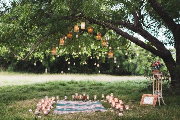 abend-hochzeits-zeremonie mit einem teppich und viel vintage lampen und kerzen am großen baum. rustikaler stil - grüne wald hochzeiten stock-fotos und bilder