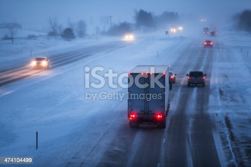 1127834626 istock photo Evening Winter Blizzard with Vehicles on Interstate Highway 474104499