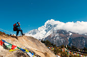 Everest Base Camp Trek. A man stands on a hill and looks at the horizon. In the background are mountains and clouds. In the frame Nepalese prayer flags with prayers.