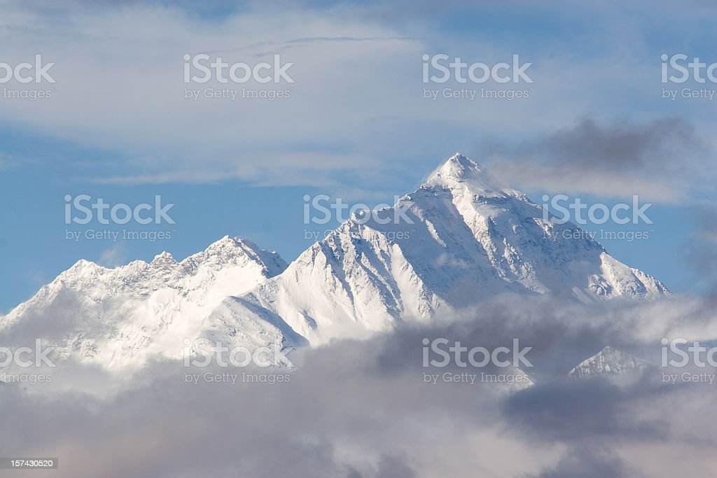 Everest Mountain , Tibetan Side. Tibetan side of Everest mountain in a rare moment of clear view through the clouds at the early morning sun in June. Telephoto shot from another mountain. Tibet, China. Adventure Stock Photo