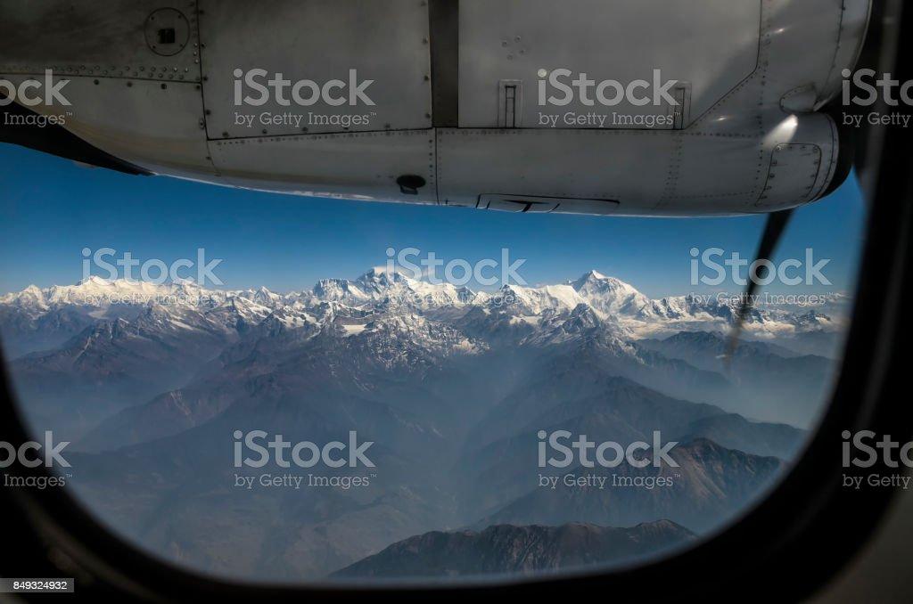 Everest Peak and Himalaya Everest mountain range panorama view through plane window stock photo