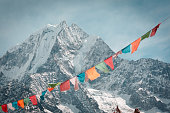 Everest trekking and hiking. Mountains of Nepal in focus. Nepalese prayer flags are blurred. Adventure in the Himalayas