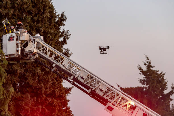 Everett WAshington, USA / 05/09/2019 - House Fire Fireman Try To Contain Fire on Roof on old Ballon Frame Home as a drone records the action stock photo