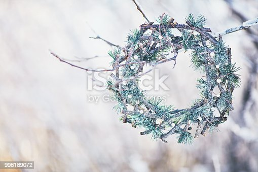 istock Evergreen wreath hanging on snow covered branches 998189072