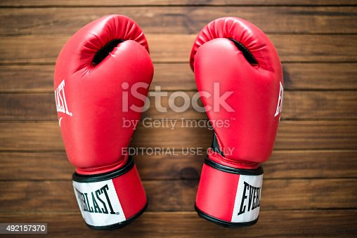 Florence, Italy - September 29, 2015: Close up of red Everlast boxing gloves apparel on a plank table Everlast is one of the most famous brand for boxing sport. Studio shot.