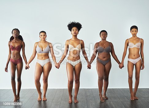 Studio shot of a diverse group of beautiful young women holding hands against a gray background
