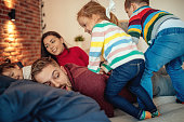 Parents playing with their kids in bed