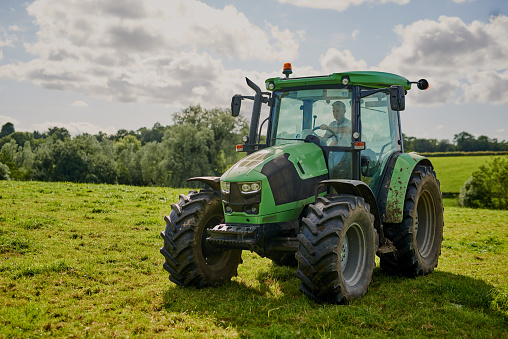 Full length shot of a green tractor on an open piece of farmland