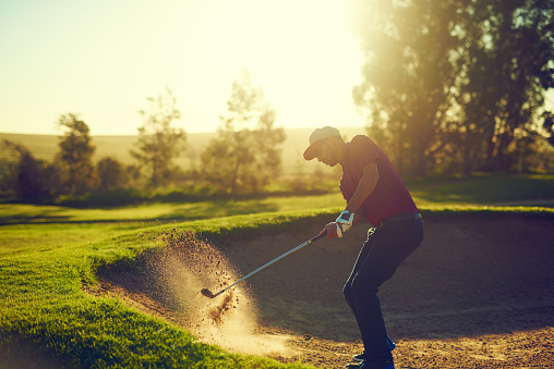 Shot of a young man hitting the ball out of the bunker during a round of golf