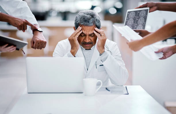 Every job can lead to burnout Shot of a mature doctor looking stressed out in a demanding work environment mental burnout stock pictures, royalty-free photos & images