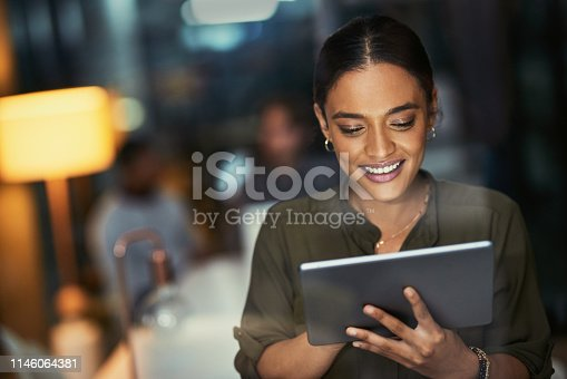 Shot of a young businesswoman using a digital tablet during a late night at work