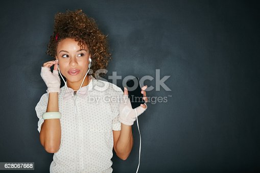 Studio shot of an attractive young woman listening to music on her phone against a gray background