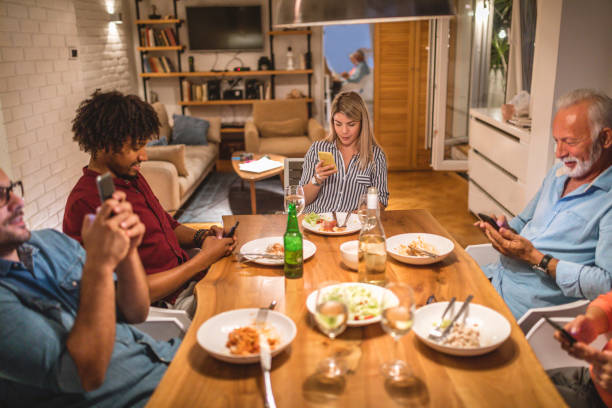 every member of the family holding a mobile phone during a dinner - eating technology stock pictures, royalty-free photos & images