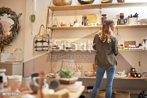 Rearview shot of a young woman looking at products on a shelf in a store